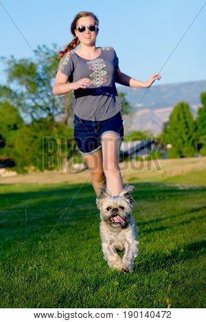girl running after small dog in the grass