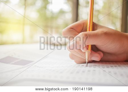 hand student testing in exercise and taking fill in exam carbon paper computer sheet with pencil at school test room education concept