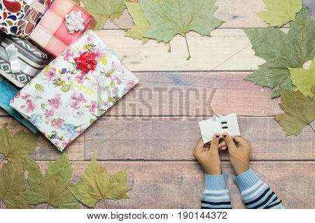 reading dedication of gifts on wooden table with autumn leaves