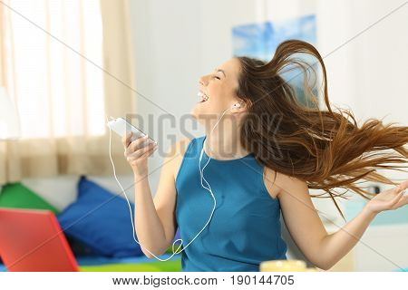 Teen listening to music and dancing holding a smart phone with her hair moving in her room
