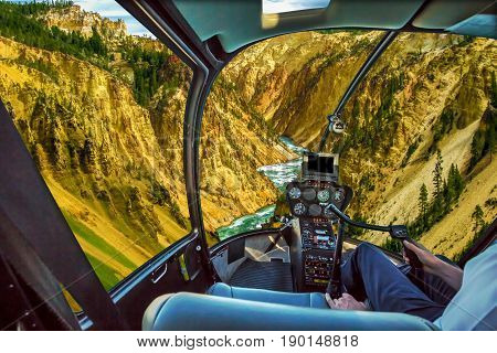 Helicopter cockpit pilot arm flight over Lower Falls, most popular waterfall in Yellowstone, located in head of Grand Canyon in Yellowstone River of Yellowstone National Park, Wyoming, United States.