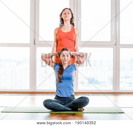 Two woman in colorful sportswear making exercise with closed eyes in yoga class. Thai massage element. Treatment, rest, relaxation, health care, medicine, spa. Big windows soft light in the background