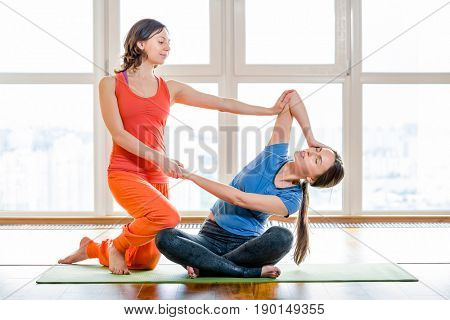 Two caucasian woman in colorful sportswear making stretching exercises sitting on yoga mat at gym. Thai massage element. Treatment, rest, relaxation, health care, spa. Big windows in the background