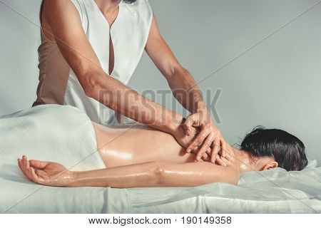 Massage oil therapy. A young professional male masseur makes Thai massage. Patient woman is lying down on a bed and is covered with white towel. Treatment, rest, relaxation, spa, health care, medicine