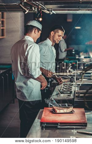 Food concept. Young handsome chefs in white uniform kindle coals and monitor temperature degree for roasting meat in interior of restaurant kitchen. Preparing traditional beef steak on barbecue oven.
