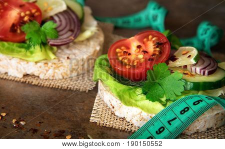 Healthy food - sandwiches rice cakes with lettuce tomato cucumber onion and parsley. With tape measure centimeter