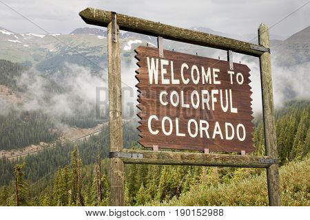 welcome to colorful Colorado roadside wooden sign with Rocky Mountains in background