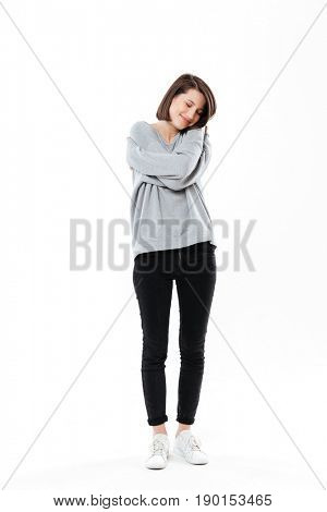 Full length portrait of a pretty young girl embracing herself while standing isolated over white background