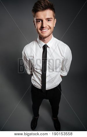 Top view full length portrait of a happy handsome man in formalwear standing and looking at camera isolated over grey background