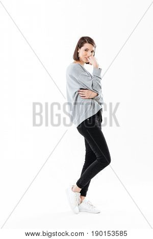 Full length side view portrait of a pensive young woman standing and looking at camera isolated over white background