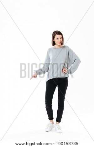 Full length portrait of a woman standing and pointing finger down at copy space isolated over white background