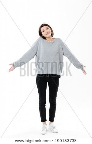 Full length portrait of a young confused girl shrugging shoulders isolated over white background