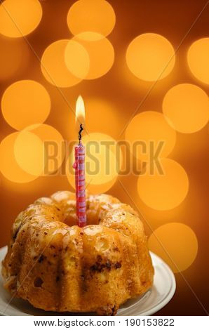birthday cupcake with colorful orange background and candle