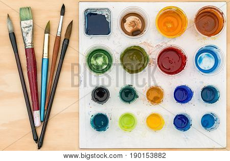 Artist paint brushes and palette with acrylic paint on wooden background
