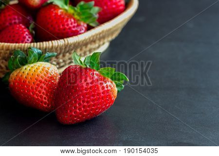 Fresh strawberry on granite background. Ripe strawberry in basket on granite table. Copy space background of strawberry for your design. Extremely exposure fruit concept background or wallpaper. Stack of strawberry on bamboo basket.