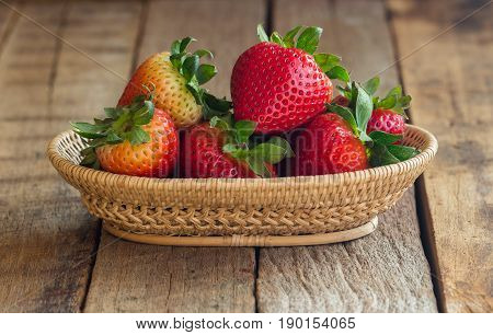 Fresh strawberries on wood background. Ripe strawberry in basket on rustic wood table. Copy space background of strawberry for your design. Natural tone style fruit concept background or wallpaper. Stack of strawberry on bamboo basket.