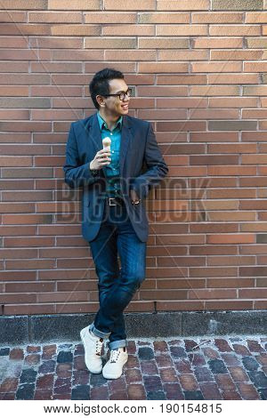 Smiling young asian man in his twenties enjoying ice cream while standing near brick wall outside on a break looking to the side, full body