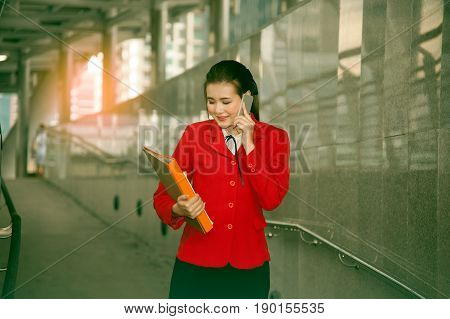 Asian Pretty woman in red suit holding document and use smart phone standing on crossing bridge landmark of Bangkok.