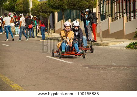Quito, Ecuador - May 06, 2017: An unidentified couple racing on a wooden car in urban road.