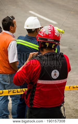 Quito, Ecuador - December 09, 2016: An unidentified group of firefighter's man waiting behind the danger tape in streets.