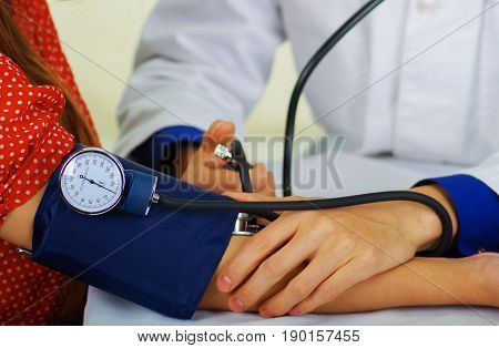 Close up of a young doctor using the stethoscope to hear the pulse while a woman is with a tensiometer in her arm, in a doctor consulting room background.