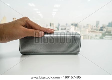 close up women left hand on modern portable bluetooth speaker for listening to music