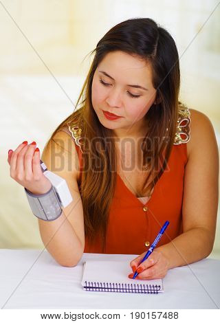 Beautiful young patient using an automatic tensiometer in her arm and taking notes of the results in his notebook, in a doctor consulting room background.