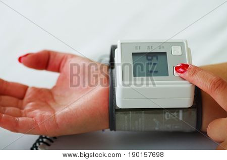 Close up of a young patient using an automatic tensiometer in her arm, in a doctor consulting room background.