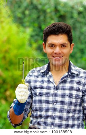Attractive smiling young builder holding a screwdriver wearing job gloves.