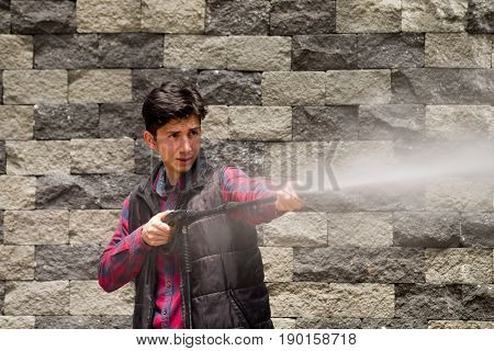 Handsome young man wearing square pattern red holding high pressure water gun, on a grey brick wall background.