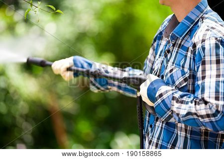 Young man wearing square pattern blue holding high pressure water gun, on a garden background.