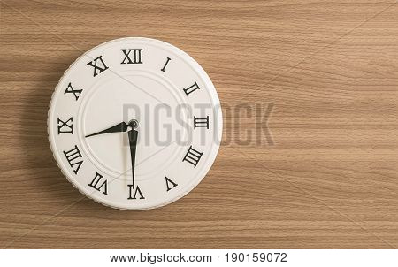Closeup white clock for decorate show half past eight o'clock or 8:30 a.m. on wood desk textured background with copy space