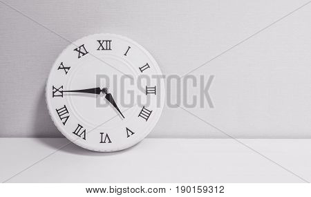 Closeup white clock for decorate show a quarter to four o'clock or 4:45 p.m. on white wood desk and wallpaper textured background in black and white tone with copy space