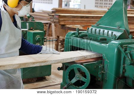 Worker is working with planing of wood machine. He is wearing safety equipment in factory