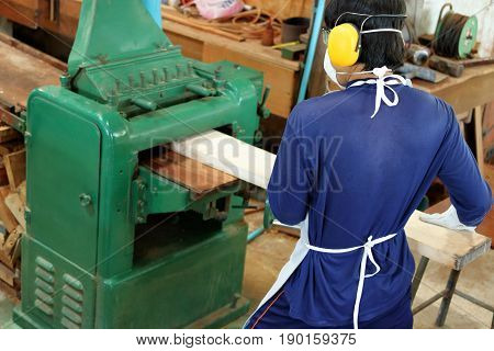 Worker is working with planing of wood machine.He is wearing safety equipment in factory Top view