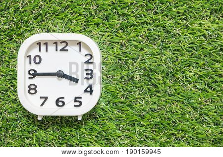 Closeup white clock for decorate show a quarter to four o'clock or 3:45 p.m. on green artificial grass floor textured background with copy space