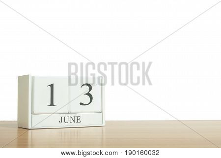 Closeup surface white wooden calendar with black 13 june word on blurred brown wood desk isolated on white background with copy space selective focus at the calendar