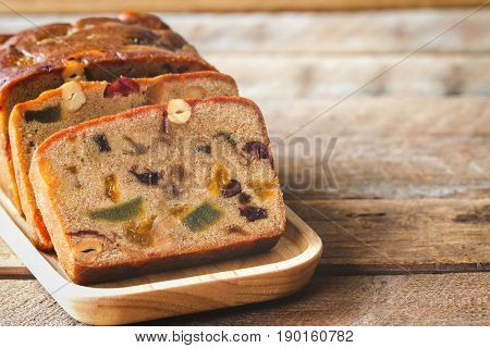 Homemade fruit cake on wood plate. Rum fruit cake with dried fruits made for Christmas celebration. Traditional homemade fruit cake for Christmas so delicious rich and moist on rustic wood table. Slice of delicious Christmas fruit cake.