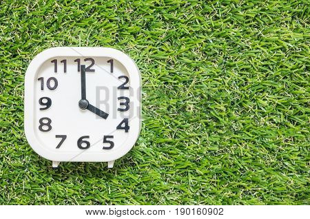 Closeup white clock for decorate in 4 o'clock on green artificial grass floor textured background with copy space