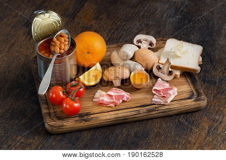 Set of food for cooking full English breakfast on the kitchen board