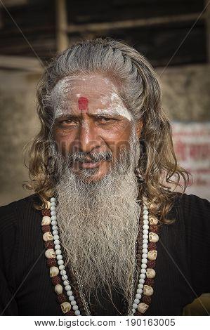 VARANASI INDIA - JANUARY 25 2017 : Portrait of Shaiva sadhu holy man on the ghats of the Ganges river in Varanasi India . Close up