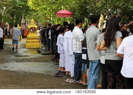 Bangkok Thailand - October 18 2016:People line up at temple in the end of Buddhist Lent Day. Before there put food to a Buddhist monk's alms bowl