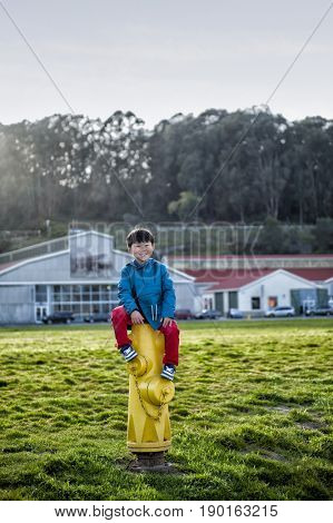 Chinese boy sitting on fire hydrant infield