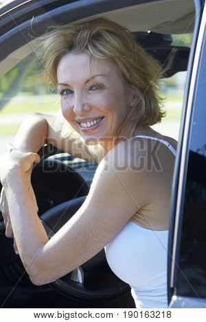 Caucasian woman smiling in driver's seat
