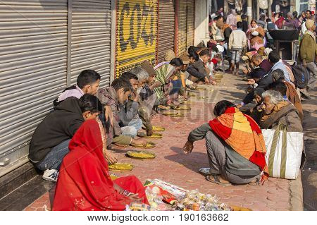 VARANASI INDIA - JANUARY 25 2017 : Unidentified poor indian people eating free food at the street near river ganges in Varanasi India
