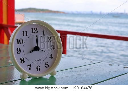 White clock at 8am on the sea background Freedom concept