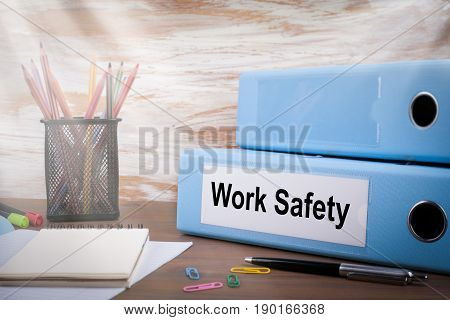 Work Safety, Office Binder on Wooden Desk. On the table colored pencils, pen, notebook paper.
