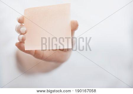 Human hand holding adhesive note. Horizontal photo