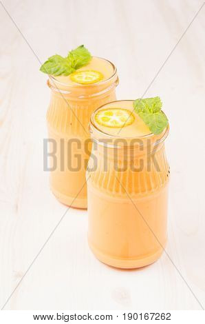 Freshly blended orange citrus kumquat fruit smoothie in glass jars with straw mint leaf cute ripe berry copy space. White wooden board background vertical.