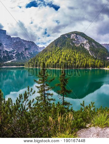 South Tyrol. Magnificent lake Lago di Braies. The concept of walking and eco-tourism. Green water reflects the surrounding mountains and forest